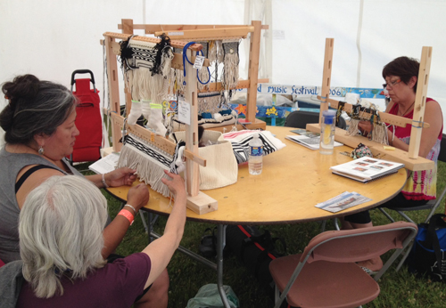 Sharon Shorty and Marge Baufeld demonstrate Ravenstail and Chilkat weaving in the Artists' Tent at the Atlin Music Festival, Atlin, B.C.
