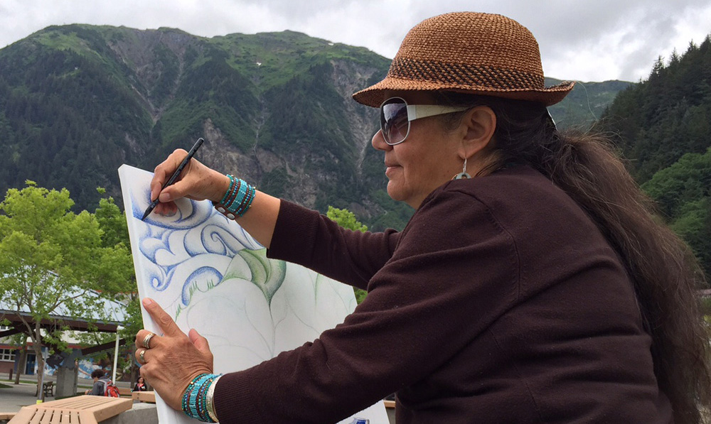 Using woodless color crayons, Clarissa does an abstract of Mt. Juneau beginning with the sky