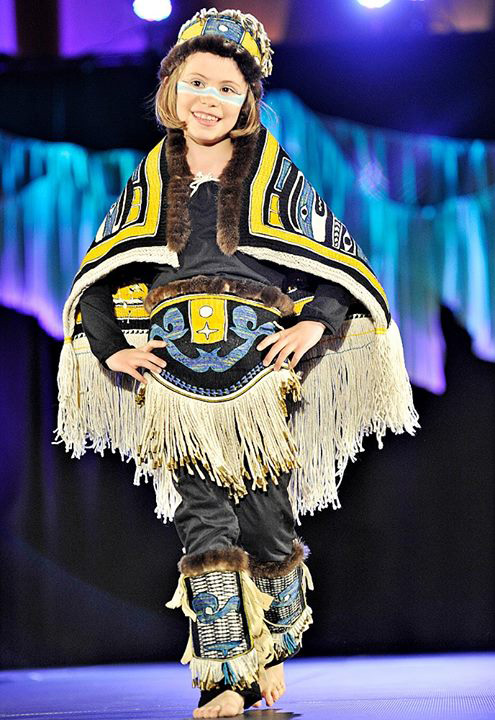 "Mariella models the 5-piece Chilkat woven ensemble ""Chilkat Child"" -- the apron, headdress and leggings are all trimmed with .22 bullet shells"