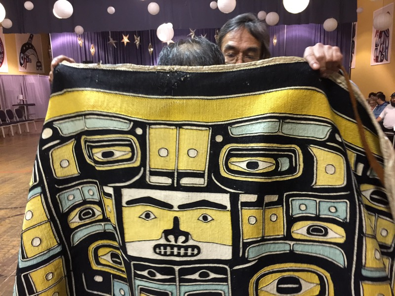 In the opening ceremonies, Bob Sam places Chilkat robe over Ed Kunz's shoulders