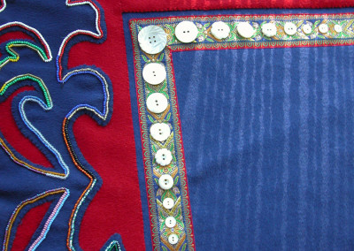 """TakDeinTaan"" Button blanket robe  Close up of beadwork (by Irene Lampe), carved mother-of-pearl buttons, and braid"